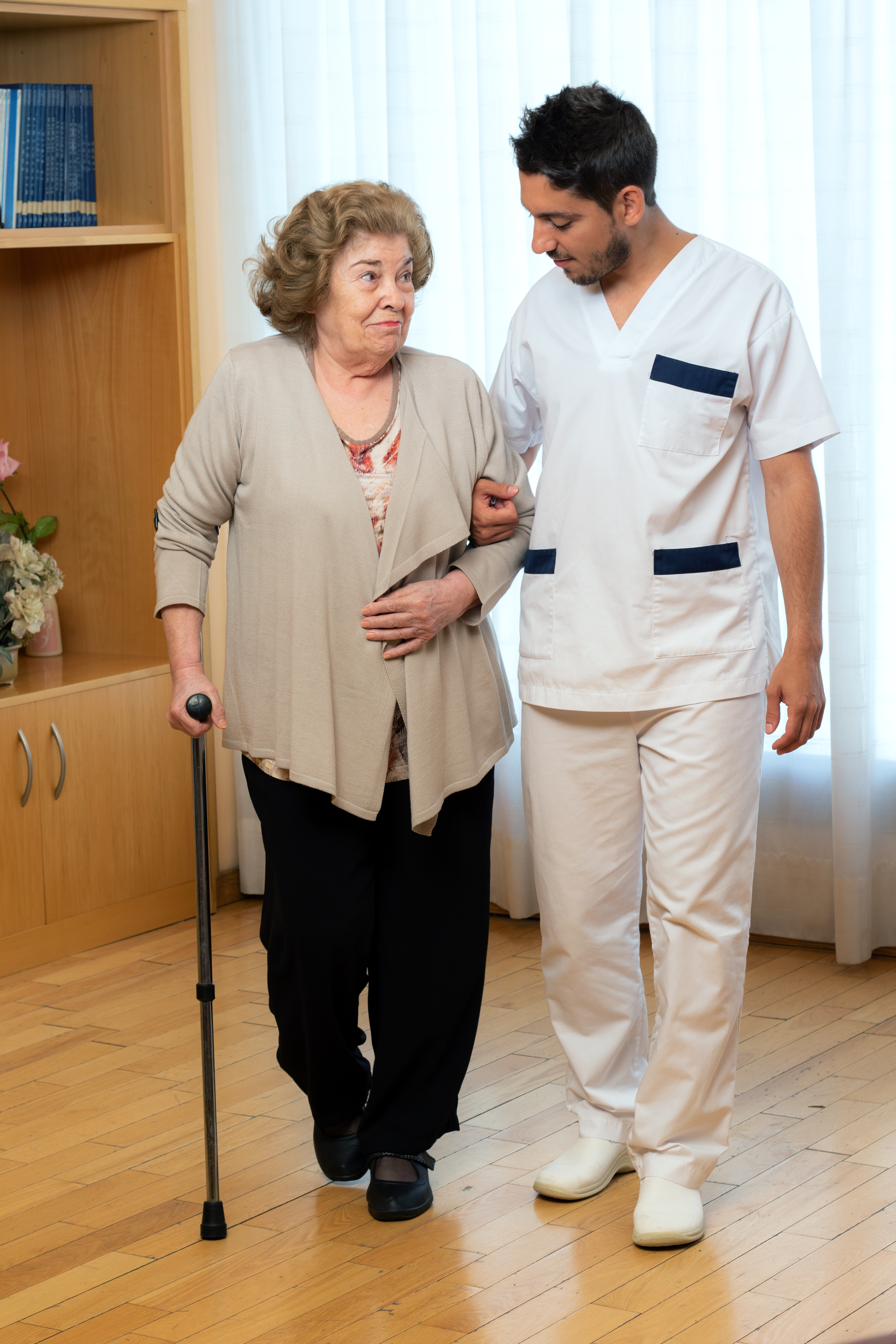 Senior woman with cane walking next to male physiotherapist at home.